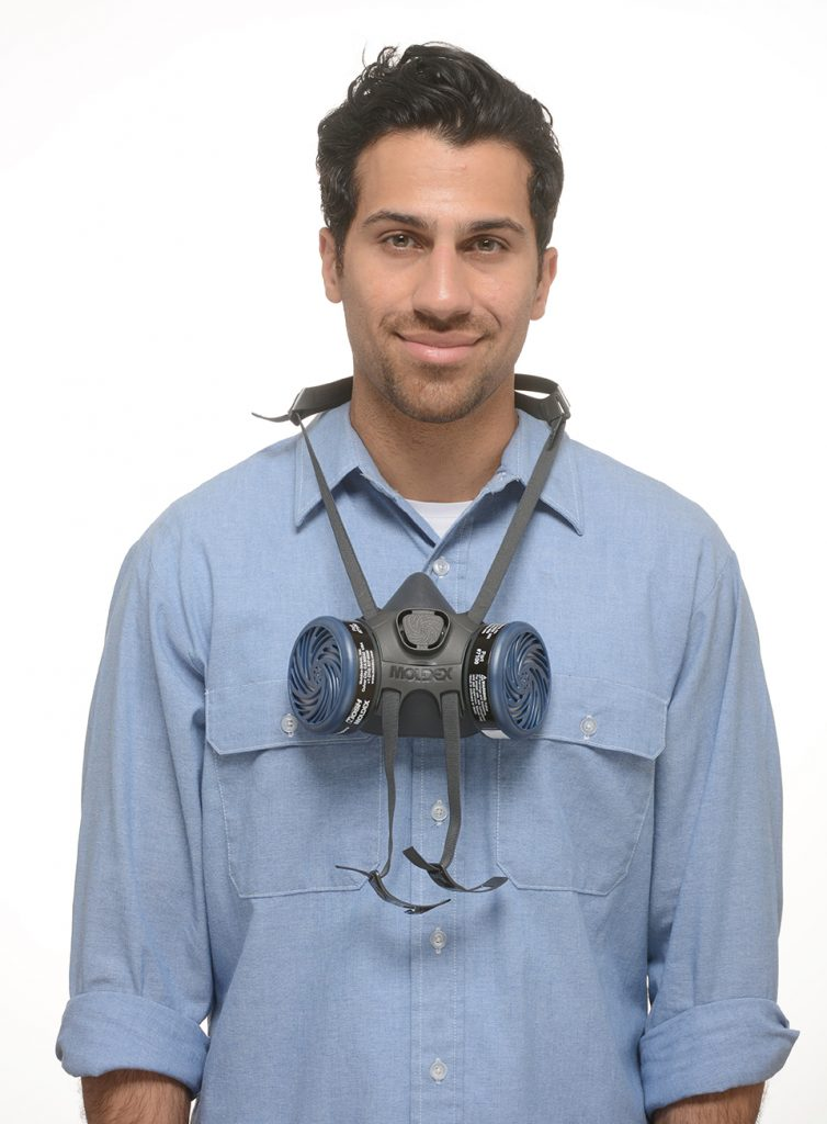 smiling man wearing reusable half-face respirator around the neck