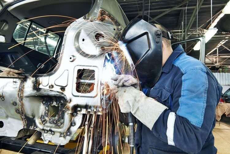 mechanic wearing face shield welding metal car parts